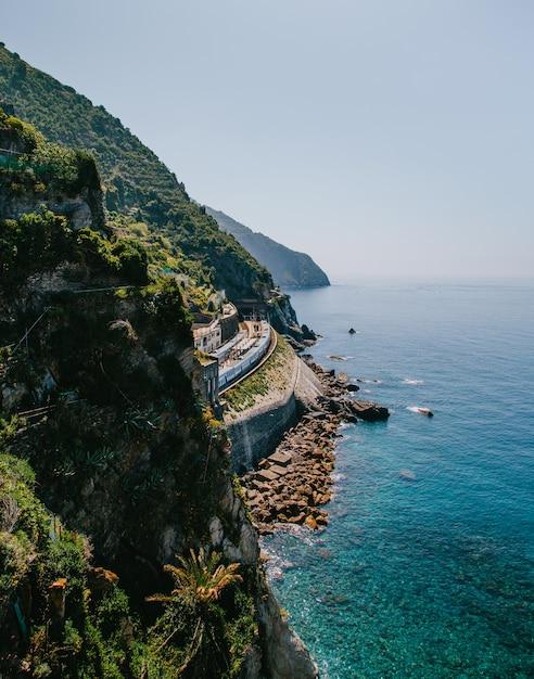 Tiro vertical de montanhas verdes pelo corpo de um oceano Foto gratuita