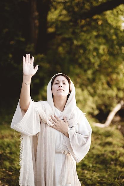 Tiro vertical de mulher vestindo uma túnica bíblica com as mãos para o céu rezando Foto gratuita