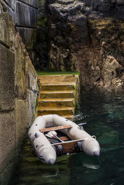Tiro vertical de um barco no lago perto da escada, cercada por belas formações rochosas Foto gratuita