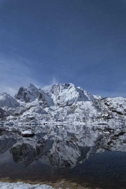 Tiro vertical de um cenário montanhoso nevado, refletindo no lago frio em lofoten, noruega Foto gratuita