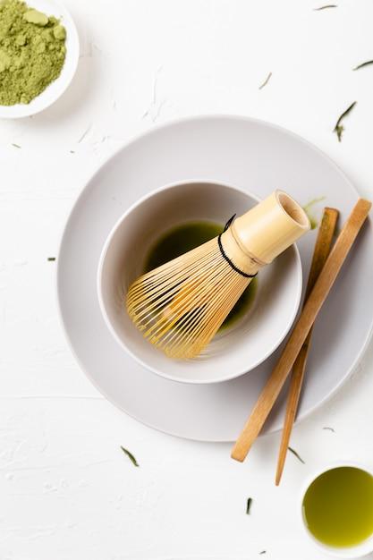 Tiro vertical de um chá matcha verde em uma mesa branca Foto gratuita