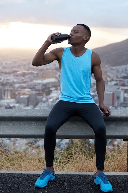 Tiro vertical de um homem afro-americano bonito em roupas esportivas bebe água após o treinamento físico, se refresca com bebida, posa sobre a colina de montanha, sente fadiga. conceito de esporte e rejuvenescimento Foto gratuita