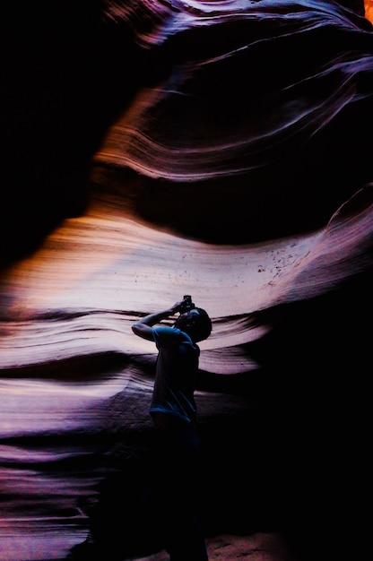 Tiro vertical de um homem com uma câmera em uma caverna tirando uma foto Foto gratuita