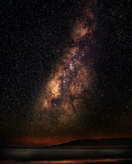 Tiro vertical de um mar sob um céu estrelado com a via láctea Foto gratuita