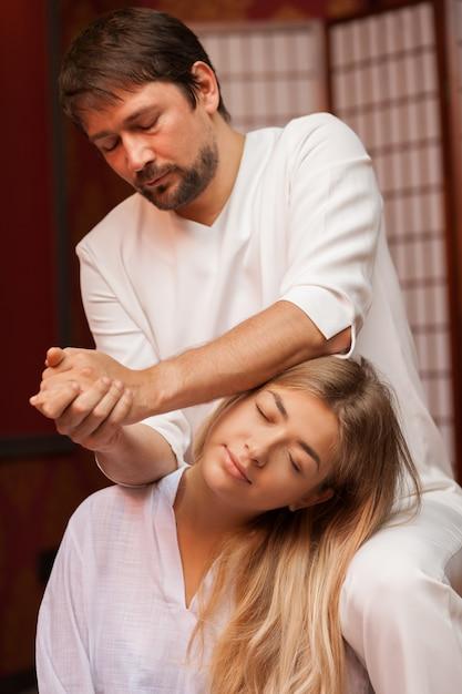 Tiro vertical de um massagista tailandês masculino maduro, esticando o pescoço de seu cliente do sexo feminino, trabalhando no centro de spa. mulher atrativa que aprecia a massagem tailandesa tradicional. acupressão, cura Foto Premium