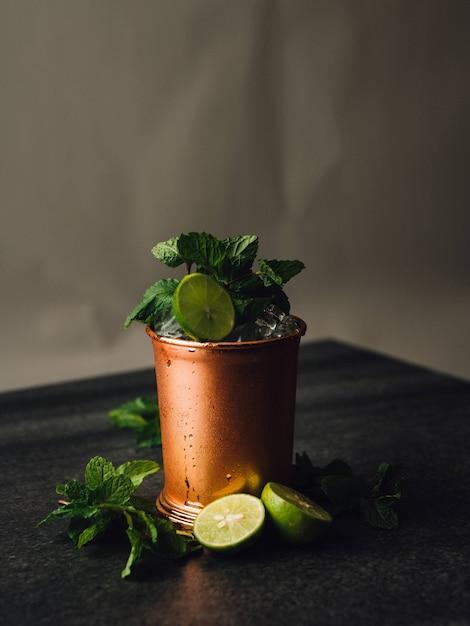 Tiro vertical de um mojito cocktail eu um copo de cobre com limão e hortelã folhas ao seu redor Foto gratuita