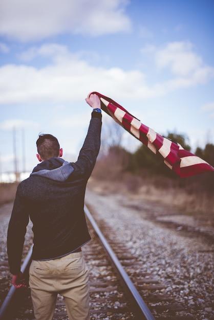 Tiro vertical de um pé masculino sobre trilhos de trem, mantendo a bandeira dos estados unidos Foto gratuita