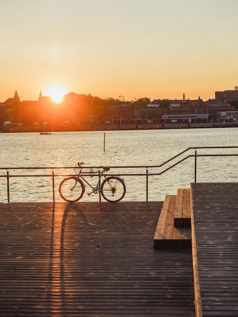 Tiro vertical de uma bicicleta estacionada na costa do mar, perto do porto durante o pôr do sol Foto gratuita