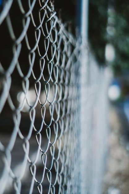 Tiro vertical de uma cerca com fio com um fundo desfocado Foto gratuita