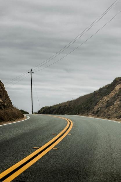 Tiro vertical de uma estrada frente e verso, rodeada por colinas com o céu cinzento nublado no Foto gratuita