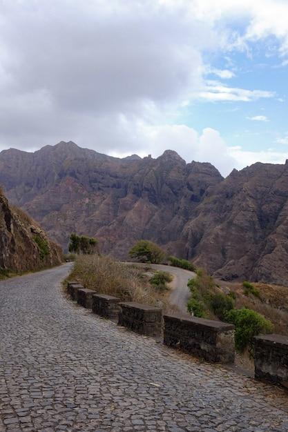 Tiro vertical de uma estrada no meio de formações rochosas sob o céu nublado Foto gratuita