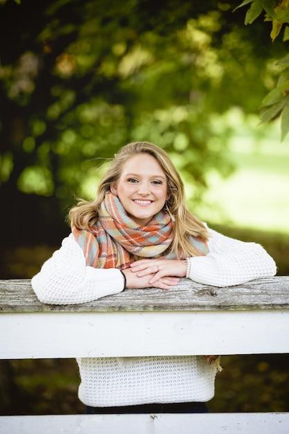 Tiro vertical de uma linda mulher loira sorridente, inclinando-se sobre uma borda de madeira Foto gratuita