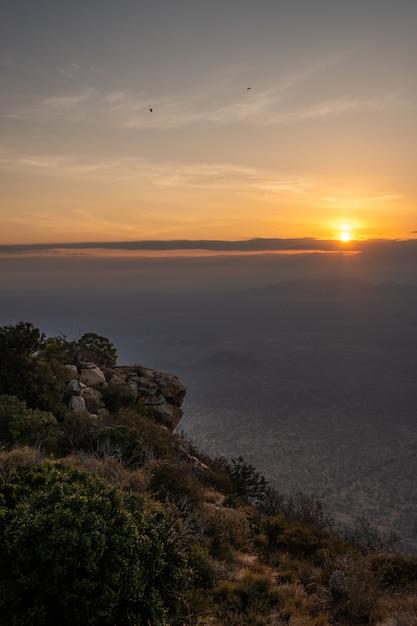 Tiro vertical de uma montanha coberta de árvores e o pôr do sol capturado no quênia, nairobi, samburu Foto gratuita