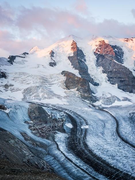 Tiro vertical de uma montanha de neve sob um céu nublado Foto gratuita