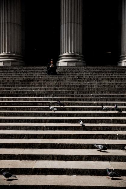Tiro vertical de uma pessoa sentada na escada perto de colunas Foto gratuita