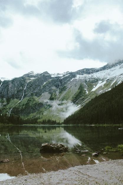 Tiro vertical de uma rocha no lago avalanche, com uma montanha arborizada Foto gratuita