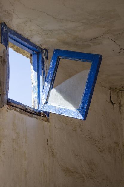 Tiro vertical de uma velha janela azul rústica prestes a quebrar e cair na sala em ruínas Foto gratuita