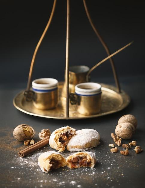 Tiro vertical de xícaras de café douradas e um jazzve com biscoitos e nozes em uma superfície preta Foto gratuita