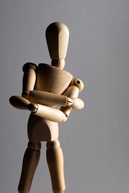 Tiro vertical do close up de uma boneca de madeira pose com os braços cruzados em pé na sombra Foto gratuita