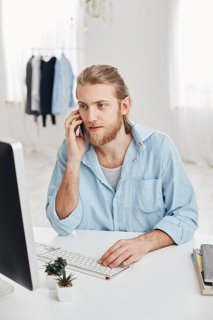 Tiro vertical do freelancer bonito caucasiano com barba e cabelo loiro, verificando informações e digitando texto promocional. empregado masculino olhando agradável tem conversa por telefone com os clientes. Foto gratuita