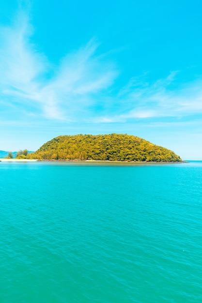 Tiro vertical do mar com uma ilha coberta de árvores sob um céu azul Foto gratuita