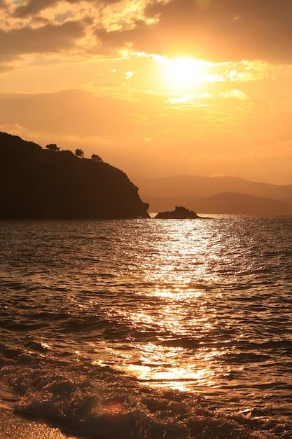 Tiro vertical do mar, rodeado por montanhas durante o pôr do sol Foto gratuita