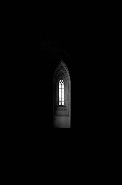 Tiro vertical em escala de cinza de uma janela no final de um corredor em forma de arco em um prédio escuro Foto gratuita