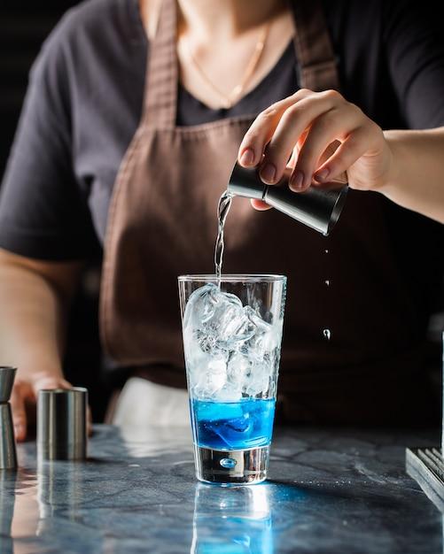 Tiro vertical seletivo closeup de uma mulher fazendo bebida alcoólica azul com gelo Foto gratuita