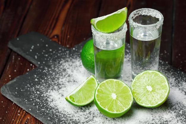 Tiros de tequila prata com fatias de limão e sal na placa de madeira Foto Premium