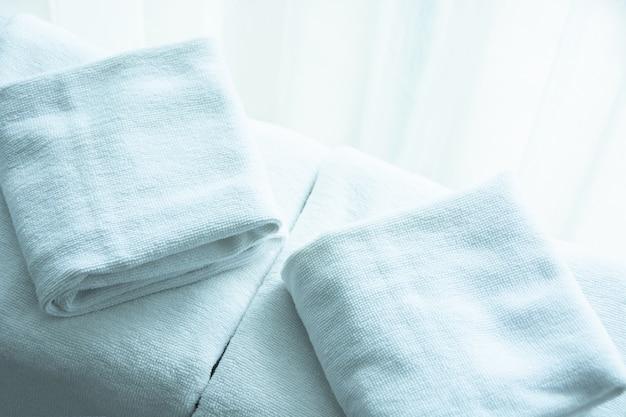 Toalha branca em tecido de colchão branco, luz suave de manhã. Foto Premium