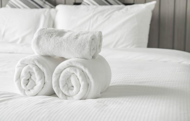 Toalha branca na decoração da cama no interior do quarto Foto gratuita
