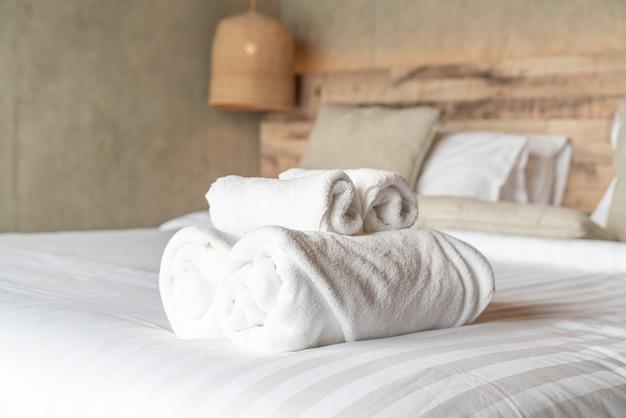 Toalha branca na decoração da cama no quarto Foto Premium