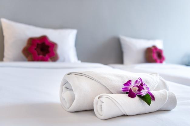 Toalha com orquídea na decoração da cama no interior do quarto para o cliente do hotel. Foto Premium