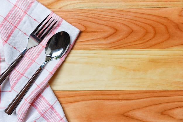 Toalha de mesa quadriculada vermelha andwhite com garfo e colher na mesa de jantar de madeira - napery Foto Premium