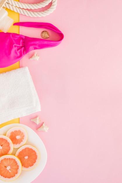 Toalha perto de garrafa com saco e maiô perto de frutas Foto gratuita