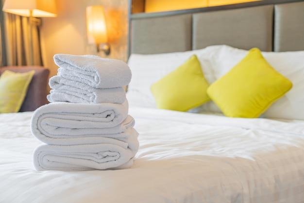 Toalhas brancas dobradas na cama Foto Premium