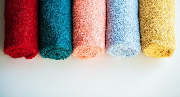 Toalhas coloridas na tabela branca com espaço da cópia no fundo da sala do banho. Foto Premium