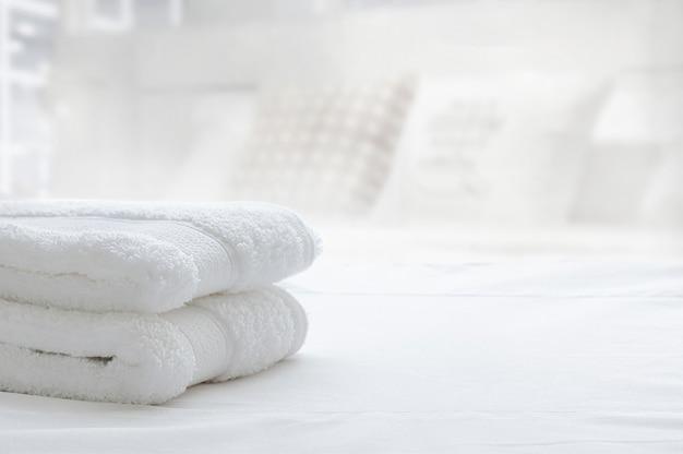 Toalhas dobradas brancas na cama branca, espaço da cópia. Foto Premium