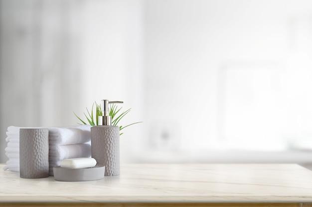 Toalhas e champô ou sabão da cerâmica na tabela de mármore superior com espaço da cópia no fundo borrado do banheiro. Foto Premium