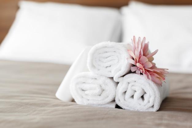 Toalhas e flor na cama no quarto de hotel Foto Premium