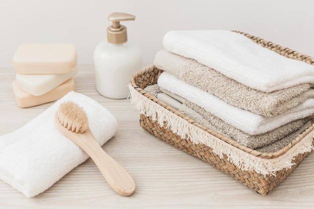 Toalhas empilhadas; escova; garrafa de sabão e cosmética na superfície de madeira Foto gratuita