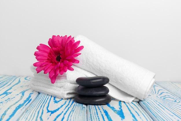 Toalhas macias limpas com flor na mesa de madeira Foto Premium