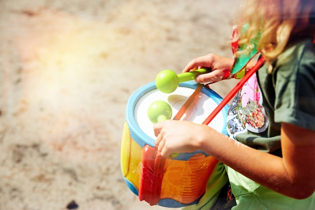 Tocando o tambor. mãos com um tambor. outra vista. africano, estrondo, batida, criança, classe, tambor, baterista, dedos, mão, acertar, instrumento, criança, música, musical, percussão, tocar, ritmo, anel, som. Foto Premium