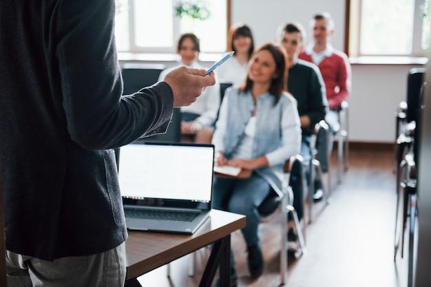Todos estão sorrindo e ouvindo. grupo de pessoas em conferência de negócios em sala de aula moderna durante o dia Foto gratuita