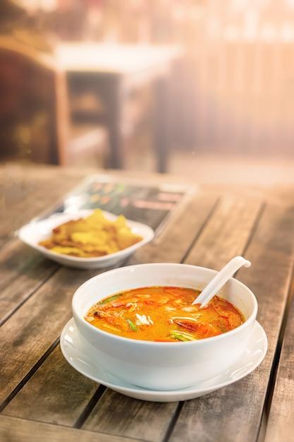 Tom yam kung, cozinha tailandesa. em uma mesa de madeira foto vertical. Foto Premium