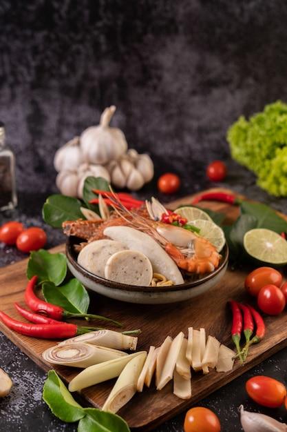 Tom yum com camarão e caranguejo com limão, pimenta, tomate, alho, capim-limão e folhas de limão kaffir. foco seletivo. Foto gratuita