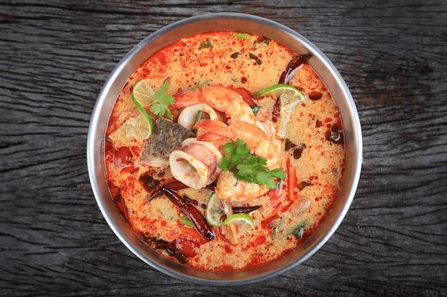 Tom yum kung ou tom yum goong, uma sopa azeda picante na vista de mesa de madeira Foto Premium