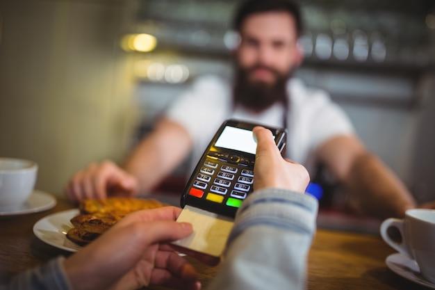 Tomada ao cliente o pagamento através do terminal de pagamento no balcão Foto gratuita