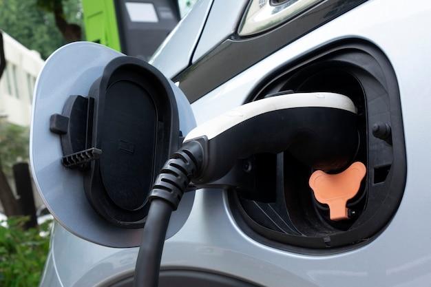 Tomada da fonte de alimentação conectada ao veículo elétrico para carregar a bateria Foto Premium
