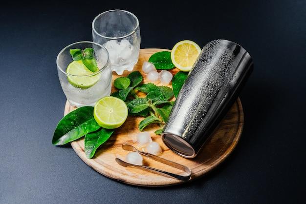 Tomada de coquetel de mojito. hortelã, limão, limão, ingredientes de gelo e utensílios de bar. Foto gratuita